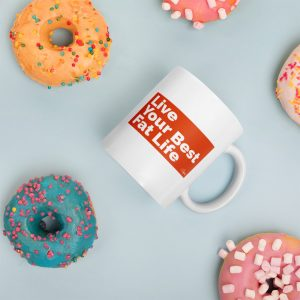 Photo of Live Your Best Fat Life Mug surrounded by colorfully decorated donuts